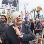 An anti-Trump protester personifies Donald Trump by wearing a blonde wig and business suit amidst a crowd of demonstrators outside at Trump rally at the San Diego Convention Center
