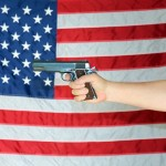 A .45 pistol is held in front of an American Flag. Represents Am