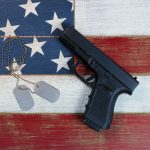Pistol and military identification tags on top of faded USA flag